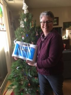 Pastor Anne holding toilet paper donation for VEAP